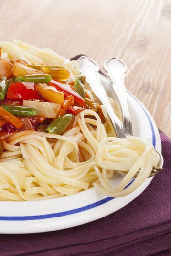 Culinary european eating. Spaghetti pasta with red tomato vegetable sauce on plate on wooden background.