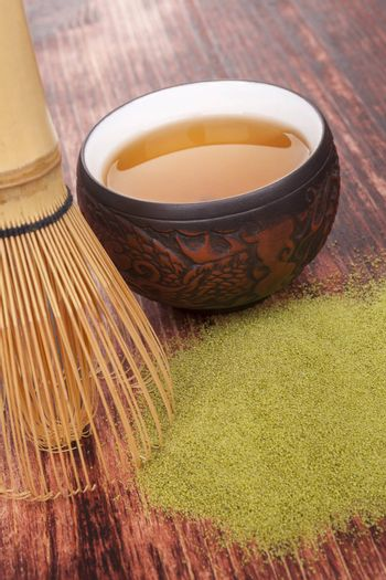 Traditional green powdered tea matcha on wooden background with bamboo chasen and cup of tea. Tea drinking.