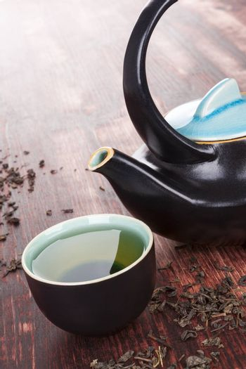 Traditional green tea ceremony. Tea in tea bowl with ceramic tea pot, dry tea crop on brown wooden background. Asian tea drinking.