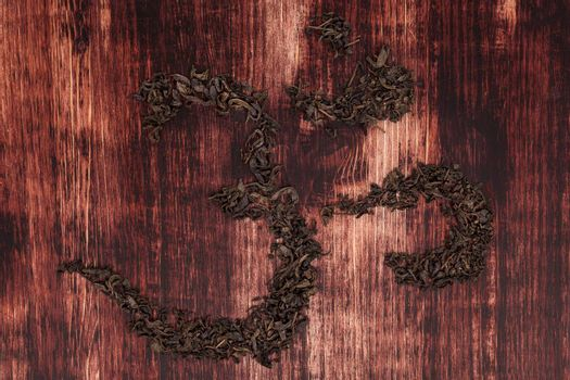 Traditional tea ceremony. Buddhist and hinduist symbol ohm. Ohm symbol from green tea on dark wooden background.