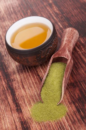 Traditional green powdered tea matcha with cup of tea on wooden background. Japanese oriental tea ceremony.