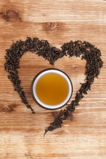 Green tea leaves in heart shape with cup of tea on wooden background. I love tea concept.