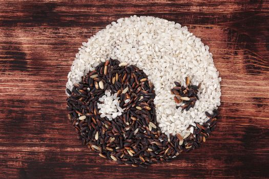 White and wild rice shaped as Yin yang symbol on dark wooden background. Traditional chinese eating and culture.