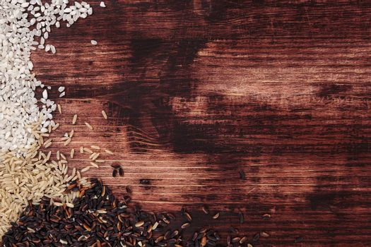 White, natural and wilde rice on dark wooden background. Healthy rice background with copy space.
