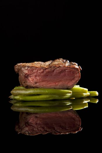 medium rare beef steak with beans on black background