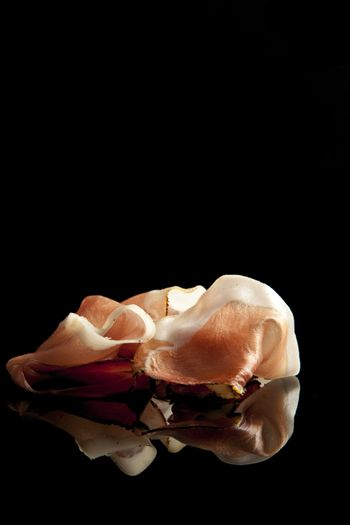 prosciutto on black background