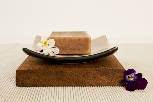 Spa still life with organic soap bar, flower blossom on a beautifull ceramics plate on wood.
