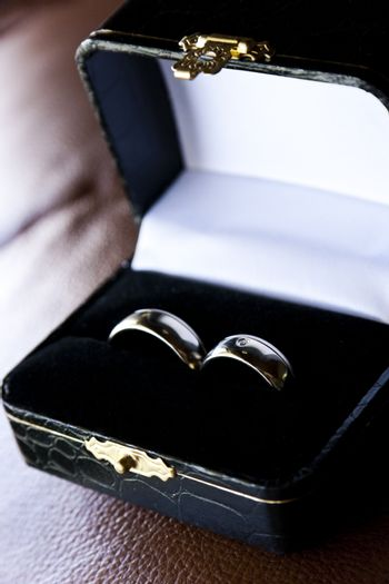Golden wedding rings in luxurious box on brown background