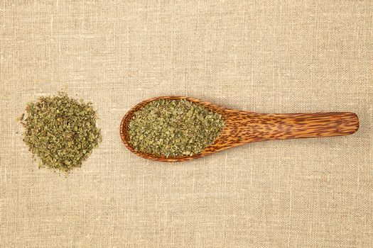Dry marjoram spice on bamboo spoon on brown background, top view.