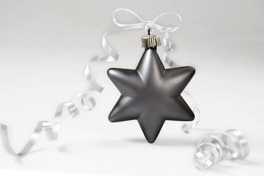 Grey christmas star with bow on white background.