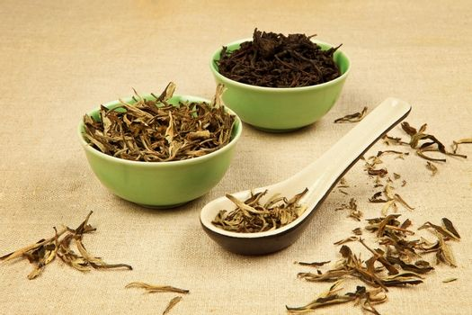 Dry green tea and black tea leaves arranged on brown background.