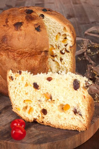 Traditional italian panettone fruit cake on brown wooden background. Culinary