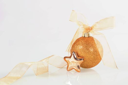 Golden christmas ball and star with ribbon on white background.