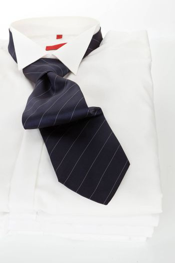 Pile of white dress shirts with red striped tie on white background. Contemporary business concept.