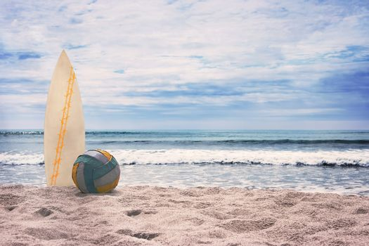 Surfboard and ball on empty beach against blue sky and turquoise ocean. Summer.