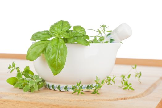 Fresh aromatic culinary cooking herbs in mortar with pestle. Basil, thyme and rosemary.