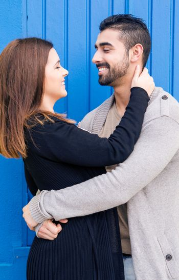 Young romantic couple hugging over blue background
