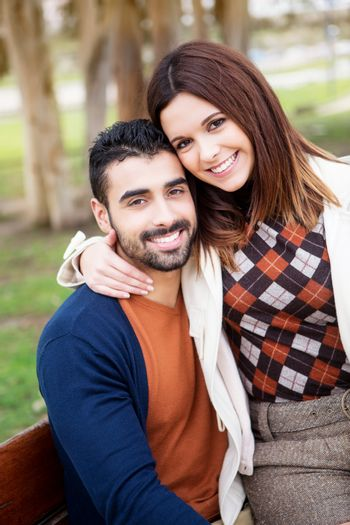 Young romantic couple on a bench in park