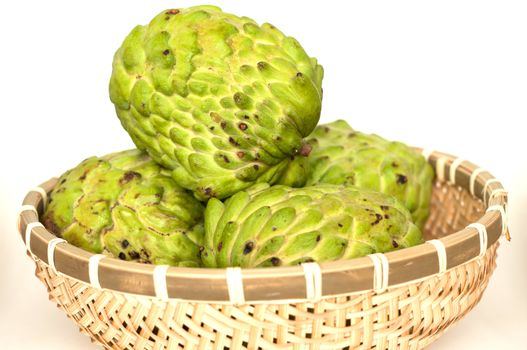 Custard apples in a bamboo basket isolated on white background