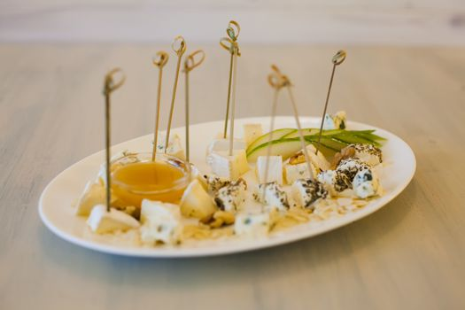 Plate with different types of cheese, honey, walnut and pear