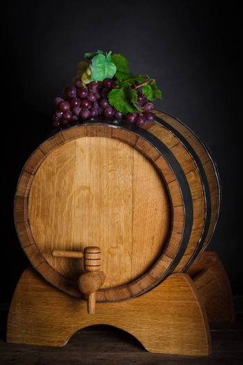 Grapes on wooden barrel with wine and copy space