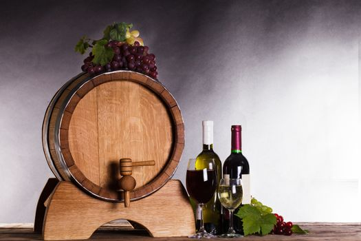 Grapes on wooden barrel with wine on a white