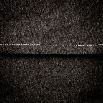 Texture of black jeans textile with sewing close up