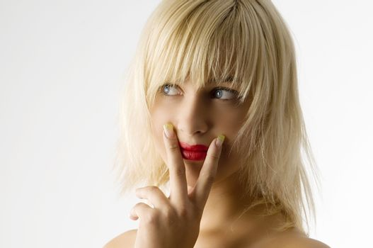 fashion portrait of blond girl with red lips and finger near mouth