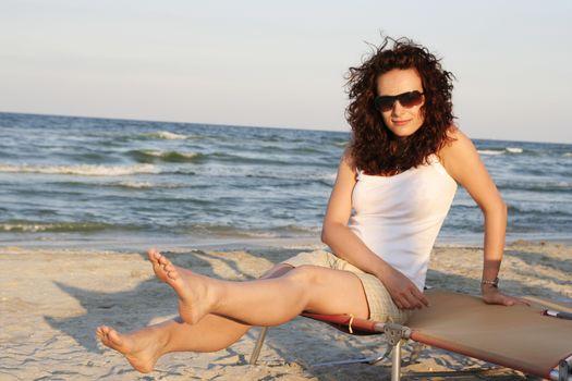 Girl sitting on a sunbed on the beach.