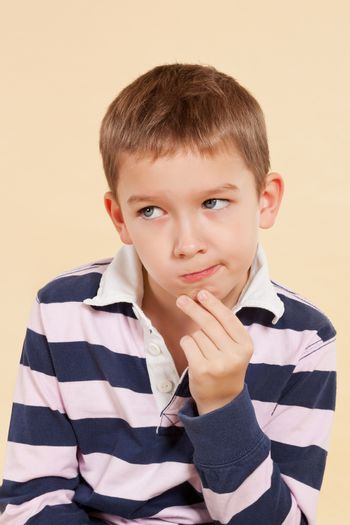 Young white boy isolated on neutral background thinking about a solution of a problem. Facial expressions concept.