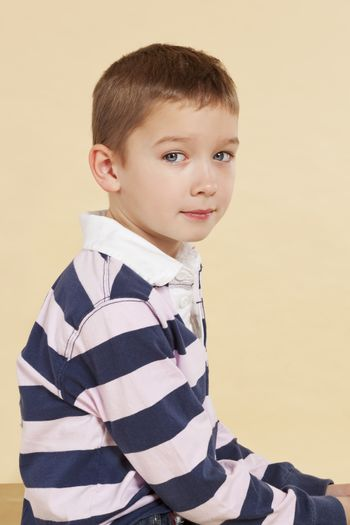 Young cute boy with hollow back sitting and looking into camera isolated. Incorrect posture concept.
