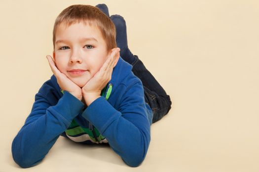 Young boy in casual cloth lying on the ground, hands on chin, smiling and looking into the camera. Youth lifestyle concept.