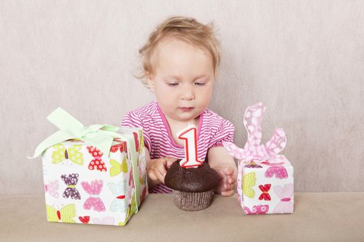 First birthday. Charming caucasian baby girl with presents and birthday cake on beige background.