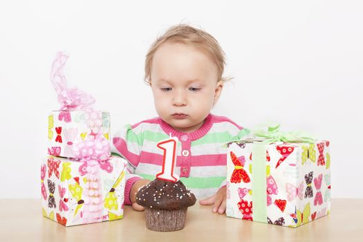 First birthday. Cute baby girl with birthday cake and birthday presents.