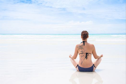 Rear view of beautiful young woman with tattoo doing yoga on beach. Wellbeing concept.
