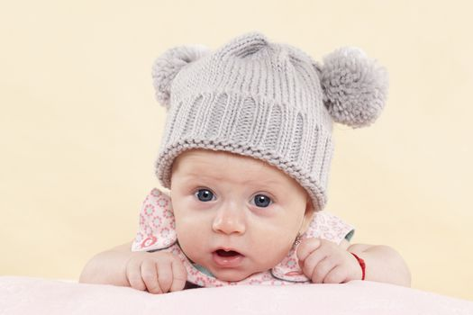 Surprised baby girl with grey hat looking into the camera isolated on neutral background. Cute newborn concept.