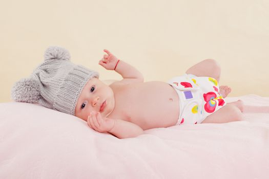 Cute baby girl with grey hat and diaper lying on blanket and looking into the camera. Beautiful newborn.