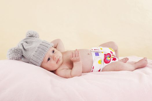 Happy naked baby with colorful diaper lying on bed and relaxing. Cute newborn baby girl.