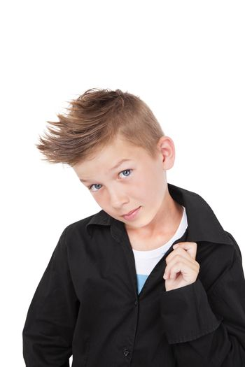 Charming casual kid in black dress shirt and fashionable haircut with cool pose isolated on white background.
