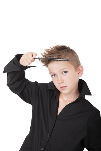 Charming young casual boy with cool haircut, holding hairbrush isolated on white background. Man fashion concept.