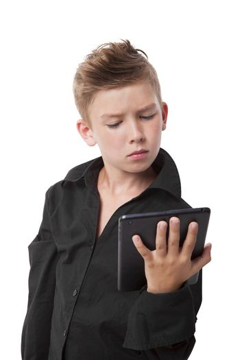 Charming boy in black dress shirt holding tablet, looking at the screen isolated on white background.