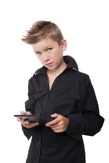 Young casual boy in fashionable black dress shirt working on tablet isolated on white.