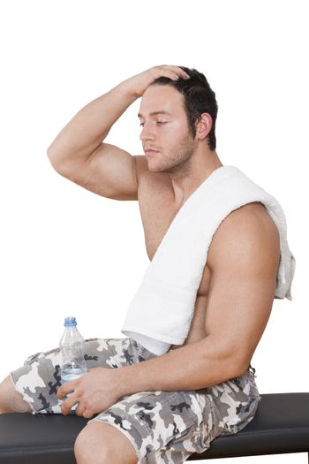 Bodybuilder resting after workout sitting on bench with water and towel isolated on white background. Sport, Fitness and Health.
