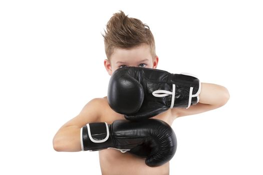 Charming boy with boxing gloves protecting his face isolated on white background. Sport and fitness.