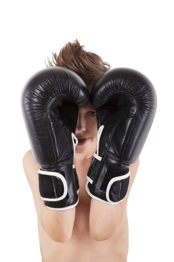 Young caucasian boy with boxing gloves protecting his face against white background. Small charming fighter.