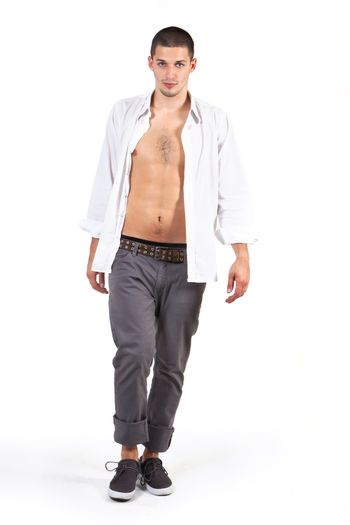 Young male attractive fashion model with white dress shirt and grey pants walking on catwalk isolated on white. Male fashion.