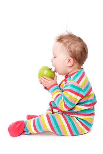 10 month old baby sitting and eating green apple isolated on white background. First teeth concept.