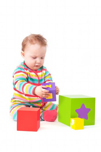 Cute one year old baby girl in colorful clothing playing with colorful blocks isolated on white background. Creativity and development concept.
