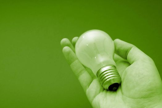Background with lit lightbulb. Isolated on green.
