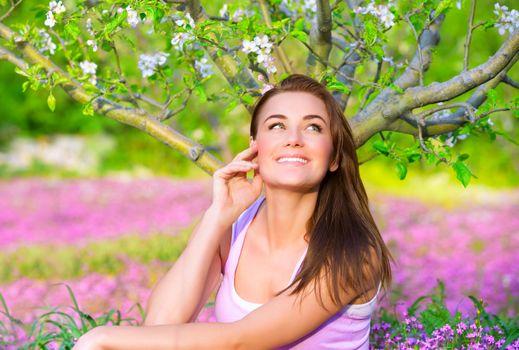 Happy woman in blooming garden
